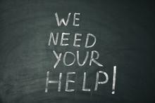 "Phrase ""We Need Your Help"" Written On Chalkboard"