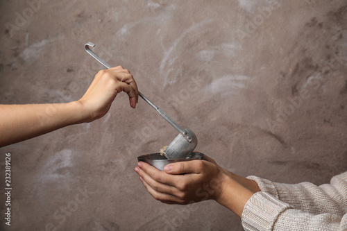 Fotomural Volunteer putting food into bowl of poor woman on color background, closeup