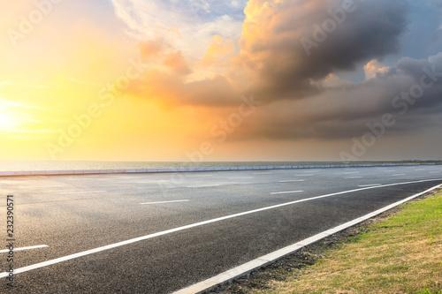 Tuinposter Zwavel geel Asphalt road and dramatic sky with coastline at sunset