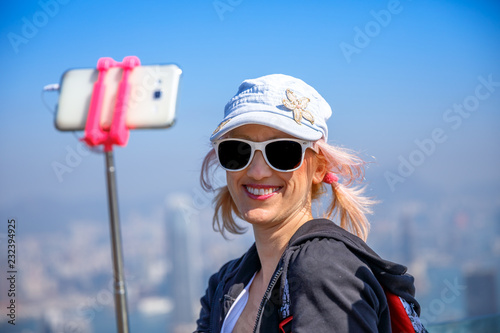 Hong Kong Victoria Peak woman taking selfie stick picture photo with
