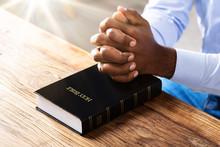 Man's Praying Hands On Bible B...