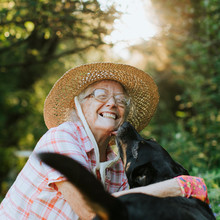 Happy Senior Woman Getting Kisses From Her Dog