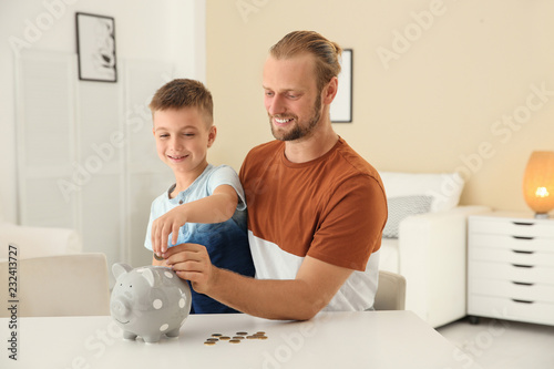 Fotografía Father and son putting coin into piggy bank at home