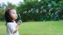 Asian Cute Little Girl Blowing To Make Many Bubbles In Public Garden At Holiday Or Vacation. Playtime Concept.