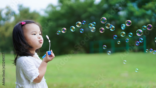 Valokuva Asian cute little girl blowing to make many bubbles in public garden at holiday or vacation