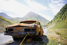 A Rusty, Burnt-out Car With No Taillights On The Road In The Mountains. In Georgia On The Sidelines Of A Rusty Broshenaya Broken Red Car In The Bright Sun