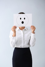 Young Woman Hiding Face Behind Sheet Of Paper With Drawn Emoticon On Light Background