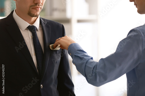 Man putting bribe in businessman's pocket. Corruption concept Canvas-taulu