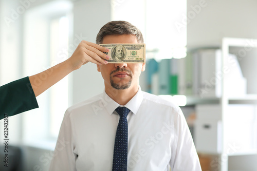 Valokuva  Woman with bribe covering eyes of businessman. Corruption concept