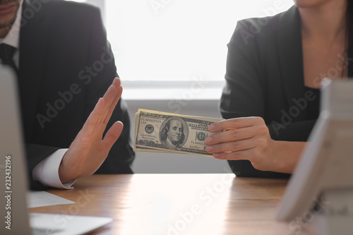 Valokuvatapetti Businessman refusing to take bribe at table. Corruption concept