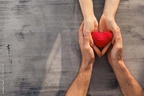 Carta da parati Loving young couple holding fabric heart on grey background