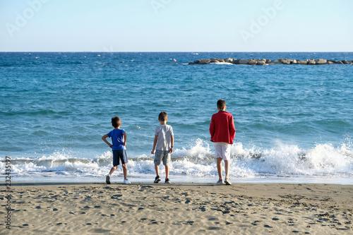 Deurstickers Cyprus Three boys on a coast of the Mediterranean sea