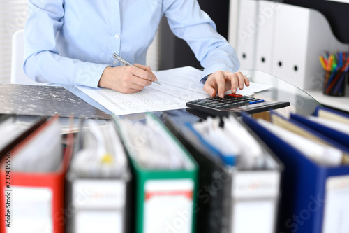 Fototapety, obrazy: Bookkeeper woman or financial inspector  making report, calculating or checking balance, close-up. Business portrait. Copy space area for audit or tax concepts