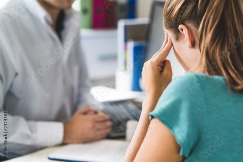 Obraz Woman suffering from bad headache or migraine. Appointment with doctor in office room. Sick and unwell lady with stress, trauma or burnout. Young patient in pain holding head with hands. Medical visit - fototapety do salonu