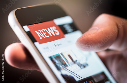 Fototapeta Online news in mobile phone. Close up of smartphone screen. Man reading articles in application. Hand holding smart device. Mockup website. Newspaper and portal on internet. obraz
