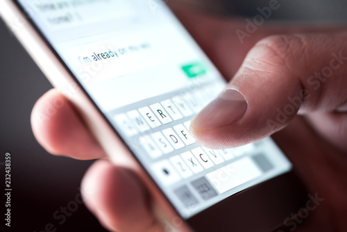 Valokuva  Man sending text message and sms with smartphone