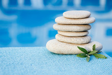 White Flat Rough Stones For Spa On Blue Blurred Background Towel And Pool. With Green Leaves Herbs. Zen Pyramid Balance.