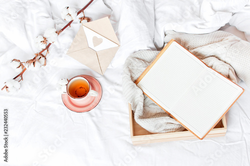 Cup of hot tea branch of cotton wooden tray knitted plaid sweater open notebook love letter in bed. Cozy morning breakfast at home. Lifestyle gentle background Copy Space autumn winter concept