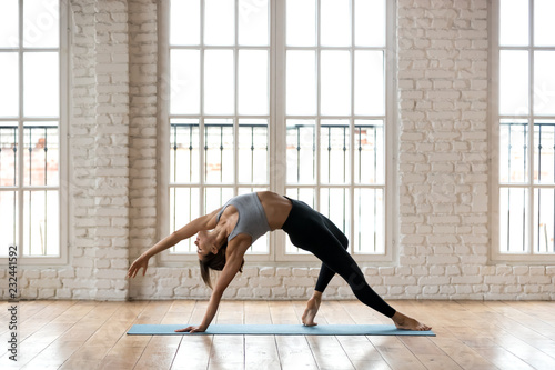 Poster Ecole de Yoga Young sporty attractive woman practicing yoga, doing Wild Thing, Flip-the-Dog exercise, Camatkarasana pose, working out, wearing sportswear, black pants and top, indoor full length, white yoga studio