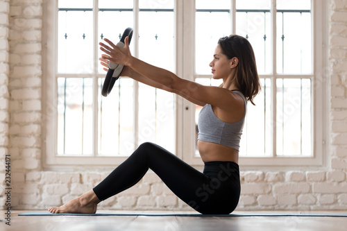 Fototapeta Sporty woman doing pilates toning exercise for arms and shoulders with ring, fitness with pilates magic circle in hands, working out wearing sportswear, indoor full length, white yoga studio or gym obraz