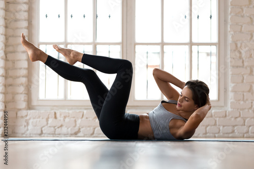 Valokuva Young sporty woman practicing, doing crisscross exercise, bicycle crunches pose,