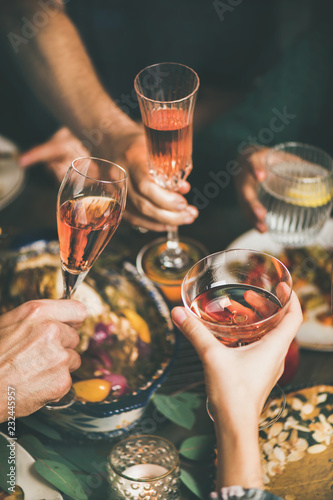 Traditional Christmas or New Year holiday celebration party. Friends or family feasting and clinking glasses with rose wine at festive table with homemade snacks