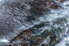 The Detailed Look At Water Runs Under Ice In A River. The Snow Is Melting From The Mountains And Flows In Creek, Close Up.