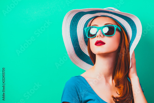 style redhead girl with makeup in blue hat and sunglasses on green background is Fototapet