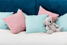 Teddy Bear Laying On The Bed With Pillows On Background