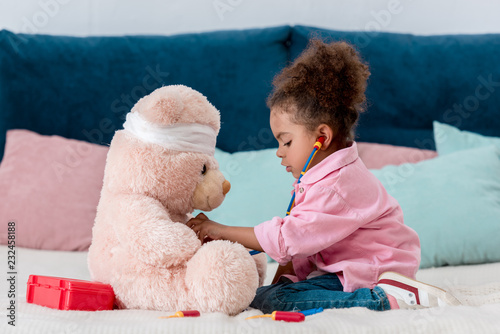 Fototapeta Little african american child in pink jacket playing the doctor  with teddy bear