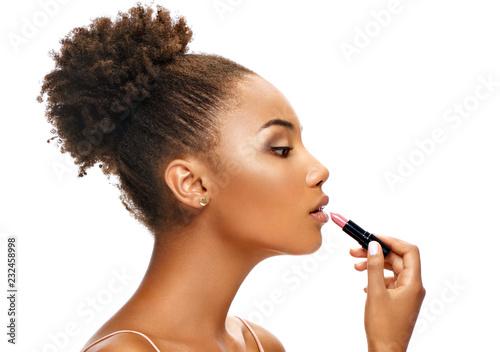 Fotografiet Beautiful girl applying lipstick on her lips