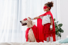 Side View Of Cute Little African American Kid And Dog Standing On The Bed