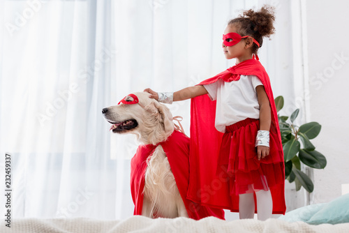 Side view of cute little african american kid and dog standing on the bed Canvas Print