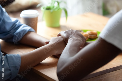Photo Black african guy holds hand of beloved girl, sitting together at table expressing showing her sincere feelings or apologizing saying sorry