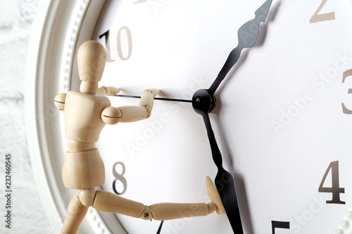 Fotografía  Wooden human figure trying to stop the arrow of the clock