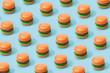Leinwanddruck Bild - Hamburger fast food pattern on pastel blue background. Minimal junk food concept.