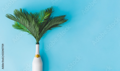 Foto  Champagne bottle with tropical green palm leaves on pastel blue background