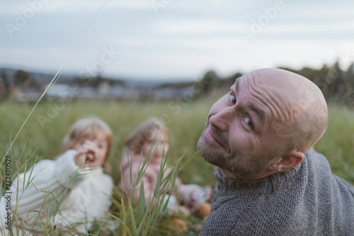 Poster Weide, Moeras Portrait of father with two children relaxing in meadow