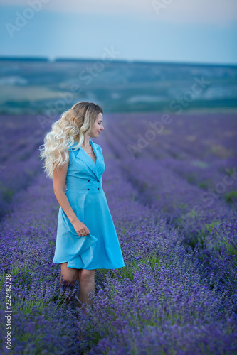 Fotografía  Sex appeal blond woman in airy blue dress enjoy life time vacation on fresh lavender field by walking or spinning around