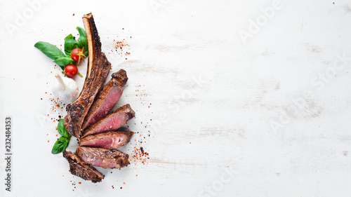 Foto auf Leinwand Steakhouse Steak on the bone. tomahawk steak On a white wooden background. Top view. Free copy space.