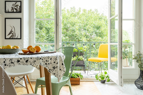 Copper mint chair placed by the table with fresh fruits and lastrico tablecloth in real photo of white room interior with balcony with plants and lights