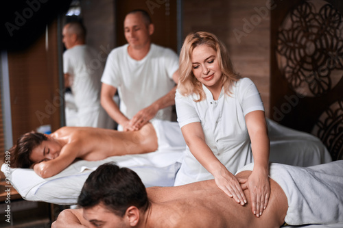 Valokuva  Relaxed clients and receiving head massage in wellness center, top view