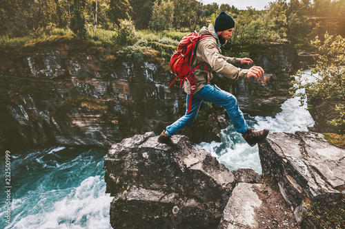 Photo Adventure man jumping on rocks over river canyon traveling active lifestyle conc