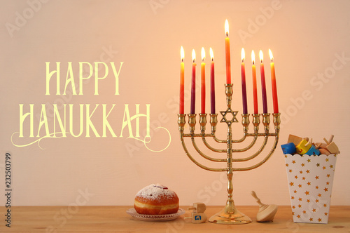 Image of jewish holiday Hanukkah background with traditional spinnig top, menorah (traditional candelabra) and burning candles.