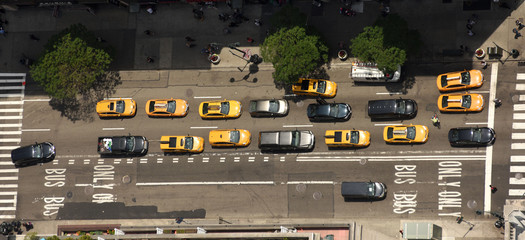 View from skyscrapers on the streets of New York City. Top view on the street with cars on the road. Yellow taxi cabs in New York City