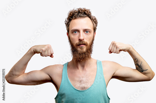 Obraz A funny mature bearded attractive guy with skinny torso, posing isolated over white studio background with raised folded hands - fototapety do salonu