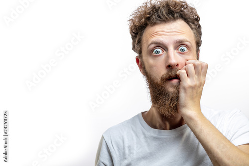 Photo  Portrait of a frustrated attractive blonde man in despair after a big collapse in his life, keeps fingers near mouth dressed casually, staring at camera with horror, isolated over white background
