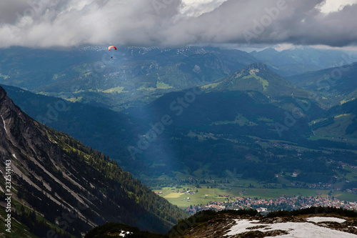 Gleitschirm an einer Bergflanke beleuchtet von einem einzelnen Sonnenstrahl