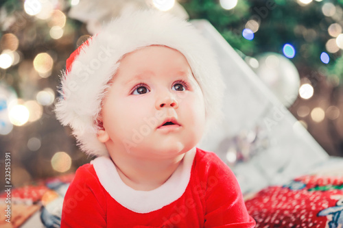 Baby first Christmas holidays. Baby with Santa hat with gift. Living room  decorated by bee05e782e60