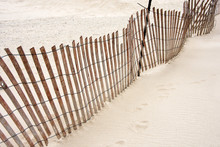 Tilted Weathered Old Wooden Fence On Beach Sand